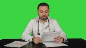 Ευτυχής αρσενικός γιατρός με τους αντίχειρες επάνω σε μια πράσινη οθόνη φιλμ μικρού μήκους