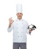 Ευτυχής αρσενικός μάγειρας αρχιμαγείρων με το cloche που παρουσιάζει εντάξει σημάδι Στοκ Εικόνες
