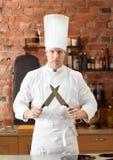Ευτυχής αρσενικός μάγειρας αρχιμαγείρων στην κουζίνα με το μαχαίρι Στοκ Εικόνες