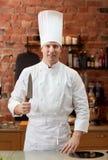 Ευτυχής αρσενικός μάγειρας αρχιμαγείρων στην κουζίνα με το μαχαίρι Στοκ Φωτογραφία