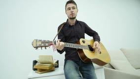 Ευτυχής αρσενικός μουσικός με μια κιθάρα, πέρα από το απομονωμένο άσπρο υπόβαθρο απόθεμα βίντεο