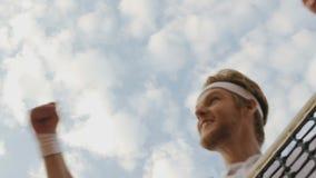 Ευτυχής αρσενικός νικητής που κάνει τη χειρονομία επιτυχίας στο υπόβαθρο μπλε ουρανού, κατώτατη άποψη φιλμ μικρού μήκους