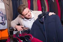Ευτυχής αρσενικός πελάτης που εξετάζει τα παλτά Στοκ εικόνες με δικαίωμα ελεύθερης χρήσης