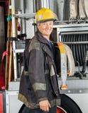 Ευτυχής αρσενικός πυροσβέστης που υπερασπίζεται το φορτηγό Στοκ φωτογραφίες με δικαίωμα ελεύθερης χρήσης