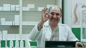 Ευτυχής αρσενικός φαρμακοποιός που παρουσιάζει allright σημάδι και stumb επάνω που χαμογελά απόθεμα βίντεο