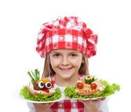Ευτυχής αρχιμάγειρας μικρών κοριτσιών με τα δημιουργικά σάντουιτς Στοκ Φωτογραφίες