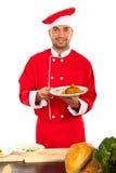 Ευτυχής αρχιμάγειρας που παρουσιάζει τρόφιμα στο πιάτο Στοκ Φωτογραφία