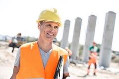 Ευτυχής αρχιτέκτονας που κοιτάζει μακριά κρατώντας την περιοχή αποκομμάτων στο εργοτάξιο οικοδομής Στοκ φωτογραφίες με δικαίωμα ελεύθερης χρήσης