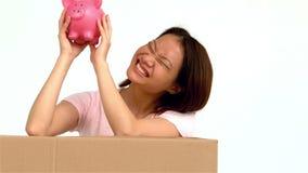 Ευτυχής ασιατική γυναίκα που τινάζει τη piggy τράπεζα απόθεμα βίντεο
