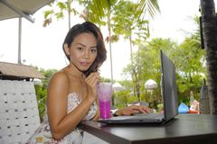 Ευτυχής ασιατική γυναίκα στην κομψή και προκλητική συνεδρίαση φορεμάτων υπαίθρια στη καφετερία θερέτρου λιμνών που έχει τον υγιή  Στοκ Εικόνα