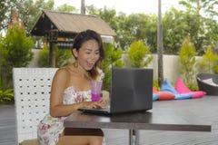 Ευτυχής ασιατική γυναίκα στην κομψή και προκλητική συνεδρίαση φορεμάτων υπαίθρια στη καφετερία θερέτρου λιμνών που έχει τον υγιή  Στοκ Φωτογραφία