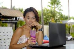 Ευτυχής ασιατική γυναίκα στην κομψή και προκλητική συνεδρίαση φορεμάτων υπαίθρια στη καφετερία θερέτρου λιμνών που έχει τον υγιή  Στοκ φωτογραφίες με δικαίωμα ελεύθερης χρήσης