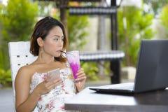 Ευτυχής ασιατική γυναίκα στην κομψή και προκλητική συνεδρίαση φορεμάτων υπαίθρια στη καφετερία θερέτρου λιμνών που έχει τον υγιή  Στοκ φωτογραφία με δικαίωμα ελεύθερης χρήσης