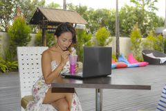 Ευτυχής ασιατική γυναίκα στην κομψή και προκλητική συνεδρίαση φορεμάτων υπαίθρια στη καφετερία θερέτρου λιμνών που έχει τον υγιή  Στοκ Φωτογραφίες