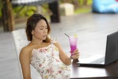Ευτυχής ασιατική γυναίκα στην κομψή και προκλητική συνεδρίαση φορεμάτων υπαίθρια στη καφετερία θερέτρου λιμνών που έχει τον υγιή  Στοκ Εικόνες