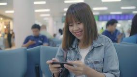 Ευτυχής ασιατική γυναίκα χρησιμοποιώντας και ελέγχοντας το smartphone της στην τελική αίθουσα περιμένοντας την πτήση της στην πύλ απόθεμα βίντεο