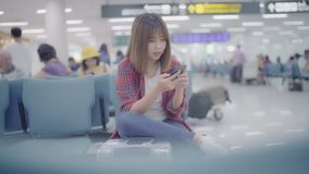 Ευτυχής ασιατική γυναίκα χρησιμοποιώντας και ελέγχοντας το smartphone της στην τελική αίθουσα περιμένοντας την πτήση της στην πύλ φιλμ μικρού μήκους