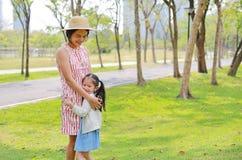 Ευτυχής ασιατική μητέρα και η κόρη της που αγκαλιάζουν στο θερινό πάρκο στοκ εικόνες με δικαίωμα ελεύθερης χρήσης