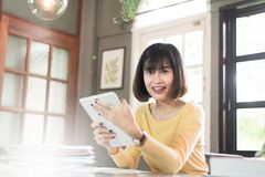 Ευτυχής ασιατική νέα επιχειρησιακή γυναίκα διασκέδασης που απασχολείται και που χρησιμοποιεί στις ταμπλέτες Στοκ εικόνες με δικαίωμα ελεύθερης χρήσης