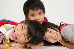 Ευτυχής ασιατική οικογένεια που αγκαλιάζει στο γκρίζο υπόβαθρο Στοκ Φωτογραφία