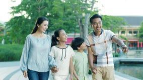 Ευτυχής ασιατική οικογένεια 4 που δείχνουν & που περπατούν προς τη κάμερα σε σε αργή κίνηση φιλμ μικρού μήκους