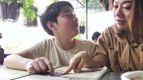Ευτυχής ασιατική οικογένεια που εξετάζει τις επιλογές στο εστιατόριο, σε αργή κίνηση 4k φιλμ μικρού μήκους