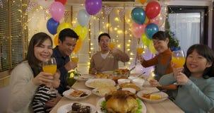 Ευτυχής ασιατική οικογένεια που κάνει την τηλεοπτική κλήση και που απολαμβάνει το γεύμα Χριστουγέννων μαζί στο σπίτι απόθεμα βίντεο