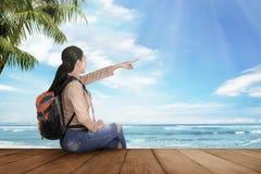 Ευτυχής ασιατική συνεδρίαση γυναικών τουριστών και απόλαυση της ωκεάνιας θέας Στοκ φωτογραφία με δικαίωμα ελεύθερης χρήσης