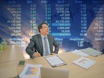 Ευτυχής ασιατική συνεδρίαση επιχειρησιακών ατόμων στο γραφείο του με το χρηματιστήριο ο στοκ εικόνες