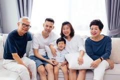 Ευτυχής ασιατική συνεδρίαση πολυμελών οικογενειών στον καναπέ μαζί, που θέτει για τις φωτογραφίες ομάδας στοκ φωτογραφίες με δικαίωμα ελεύθερης χρήσης