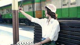 Ευτυχής ασιατικός επιβάτης γυναικών με την περιστασιακή λήψη selfie με έξυπνο κινητό τηλέφωνο στις ράγες σταθμών τρένου για το τα φιλμ μικρού μήκους