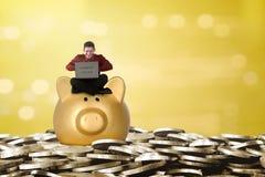 Ευτυχής ασιατικός επιχειρηματίας που χρησιμοποιεί το lap-top επάνω από τη piggy τράπεζα Στοκ Εικόνες