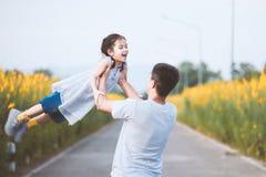 Ευτυχής ασιατικός πατέρας που κρατά το παιδί του περιστρέφοντας γύρω με τη διασκέδαση Στοκ Εικόνες