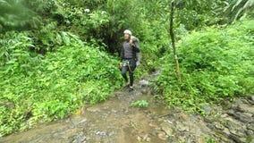 Ευτυχής ασιατικός τουρίστας που γλιστρά στον καταρράκτη ενώ Canyoning φιλμ μικρού μήκους