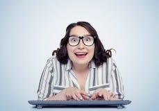 Ευτυχής αστείος προγραμματιστής κοριτσιών στα γυαλιά με το πληκτρολόγιο μπροστά από τον υπολογιστή Στοκ Εικόνες
