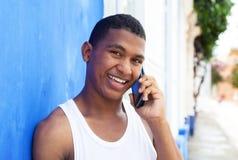 Ευτυχής λατινικός τύπος στο τηλέφωνο μπροστά από έναν μπλε τοίχο Στοκ Εικόνα
