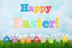 Ευτυχής αφίσα Πάσχας με τη σειρά των αυγών λαγουδάκι στη χλόη Στοκ Εικόνες
