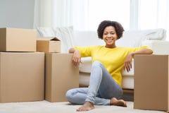 Ευτυχής αφρικανική γυναίκα με τα κουτιά από χαρτόνι στο σπίτι Στοκ Φωτογραφία