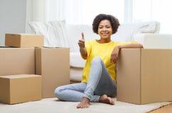 Ευτυχής αφρικανική γυναίκα με τα κουτιά από χαρτόνι στο σπίτι Στοκ φωτογραφία με δικαίωμα ελεύθερης χρήσης