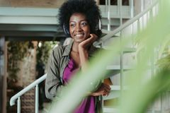 Ευτυχής αφρικανική γυναίκα που φορά τα ακουστικά και που τοποθετεί στα σκαλοπάτια στοκ φωτογραφία με δικαίωμα ελεύθερης χρήσης