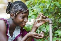 Ευτυχής αφρικανική μαθήτρια που απολαμβάνει το καθαρό νερό από μια βρύση σε Bama Στοκ Φωτογραφία