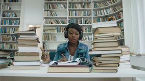 Ευτυχής αφρικανική νέα μουσική ακούσματος γυναικών στο ακουστικό γράφοντας τη διάλεξη για το πανεπιστήμιο φιλμ μικρού μήκους