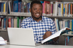 Ευτυχής αφρικανικός άνδρας σπουδαστής με το lap-top στη βιβλιοθήκη Στοκ Φωτογραφίες