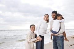 Ευτυχής αφρικανικός-αμερικανική τετραμελής οικογένεια στην παραλία στοκ εικόνες