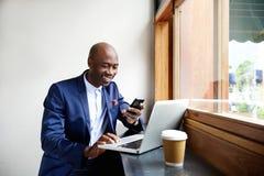 Ευτυχής αφρικανικός επιχειρηματίας που χρησιμοποιεί το τηλέφωνο στον καφέ Στοκ εικόνα με δικαίωμα ελεύθερης χρήσης