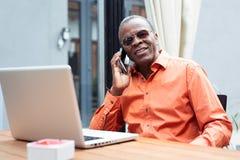 Ευτυχής αφρικανικός επιχειρηματίας που χρησιμοποιεί το τηλέφωνο στον καφέ Στοκ φωτογραφία με δικαίωμα ελεύθερης χρήσης