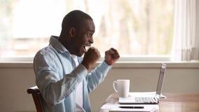 Ευτυχής αφρικανικός νεαρός άνδρας που διαβάζει στις μεγάλες ειδήσεις το σε απευθείας σύνδεση χρησιμοποιώντας lap-top απόθεμα βίντεο