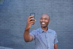 Ευτυχής αφρικανικός τύπος που παίρνει ένα selfie με το τηλέφωνο κυττάρων του Στοκ εικόνες με δικαίωμα ελεύθερης χρήσης