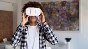 Ευτυχής αφροαμερικανός νεαρός άνδρας που χρησιμοποιεί τα γυαλιά εικονικής πραγματικότητάς του στεμένος στο σπίτι