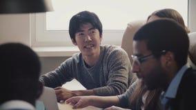 Ευτυχής βέβαιος ιαπωνικός νέος ανεξάρτητος επιχειρηματίας που μοιράζεται τις ιδέες, που χαμογελούν στη multiethnic συνεδρίαση των απόθεμα βίντεο